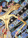 Wayang Kulit puppet on batik. An image of an antique ethnic Indonesian Wayang Kulit puppet, ornately decorated and hand crafted, placed on a piece of floral royalty free stock images