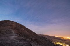 Waypath in the mountains near of Eilat city in the desert in the Israil in the evening with blue sky and city lights royalty free stock photography