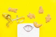 Ways for lose weight. Sport. Cookies in shape of yoga asans near scale and measuring tape on bright yellow background. Top view stock photo