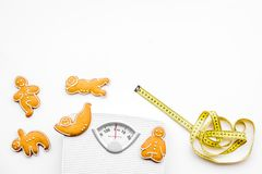 Ways for lose weight. Sport. Cookies in shape of yoga asans near scale and measuring tape on white background top view.  royalty free stock photo