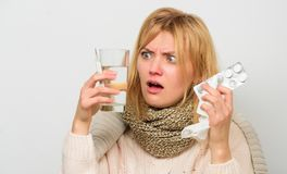 Ways to feel better fast. Flu home remedies. Get rid of flu. Woman wear warm scarf because illness or flu. Girl hold. Glass water tablets and thermometer light royalty free stock photos