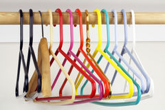 Ways to Hang. A colorful variety of clothes hangers on a wooden rod Royalty Free Stock Image