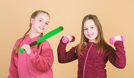 Ways to help kids find sport they enjoy. Girls cute kids with sport equipment dumbbells and baseball bat. We love sport. Child might excel in completely stock photography