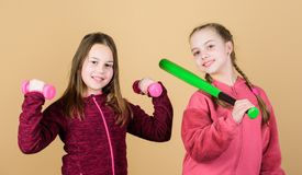 Ways to help kids find sport they enjoy. Girls cute kids with sport equipment dumbbells and baseball bat. We love sport. Child might excel in completely stock image