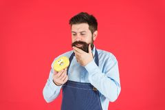 Ways to reduce hunger and appetite. Hipster bearded baker hold glazed donut on red background. Cafe and bakery concept. Sweet donut from baker. Man bearded stock photos