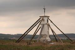 Wayside cross. Straighten wayside cross - repaired statue in the field Royalty Free Stock Image
