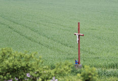 Wayside cross with figure of christ at a field Royalty Free Stock Image