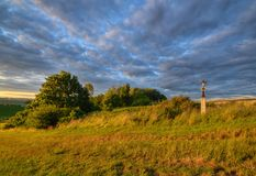 Wayside cross in meadow. Abandoned wayside in the meadow at sunset Royalty Free Stock Photos