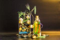 waza z kamieniami aromatycznymi butelka i jasnożółty światło na ciemnym backround obrazy royalty free
