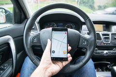 Waze. Nitra, Slovakia, april 7, 2017: Driver holding smartphone with Waze gps navigation application behind the driving wheel in car Royalty Free Stock Photo