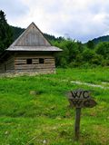 WC all around. A funny road sign in front of an unfinished wooden cottage in the mountains Royalty Free Stock Images
