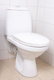 WC pan in white tiled bathroom Royalty Free Stock Image