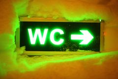 WC sign with arrow in snow royalty free stock image