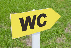 WC sign pointing direction on a green grass Stock Photography