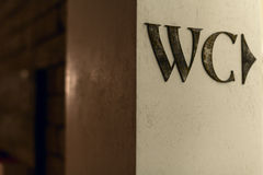 WC sign. On the rusted beige wall Stock Image