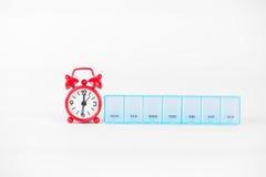 Wöchentlicher Pillenkasten und rote Uhr zeigen Medizinzeit Stockbild