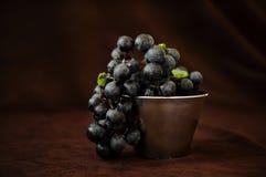 Wciąż żyć winogrona w filiżance na brown tkaniny tle Obrazy Royalty Free