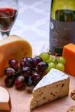 Wciąż życia czerwonego wina, roquefort sera, czerwieni i zieleni winogrona na drewnianym talerzu, Obrazy Stock