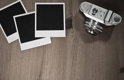 Wciąż życia trzy pustego miejsca fotografii natychmiastowe ramy na starym drewnianym tle z starą retro rocznik kamerą z kopii prz Obrazy Royalty Free
