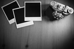 Wciąż życia trzy pustego miejsca fotografii natychmiastowe ramy na starym drewnianym tle z starą retro rocznik kamerą z kopii prz Obraz Stock