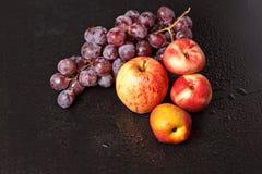 Wciąż życie brzoskwinie jabłka i winogrona Zdjęcia Royalty Free