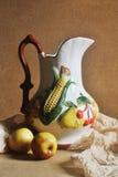 Wciąż życie fotografia dzbanek z owoc rzeźbi i dwa jabłek om drewnianym tłem Zdjęcia Royalty Free