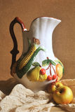 Wciąż życie fotografia dzbanek z owoc rzeźbi i dwa jabłek om drewnianym tłem Zdjęcia Stock