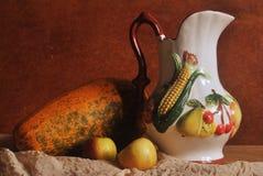 Wciąż życie fotografia dzbanek z owoc rzeźbi i dwa jabłek om drewnianym tłem Obraz Stock