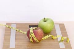 Wciąż życie fotografia z dwa jabłkami, taśmy mesaure i skala, zdjęcia stock