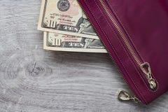 Wciąż życie gotówka Bordoscy rzemienni portfla i amerykanina dolary na drewnianym tle Fotografia Stock