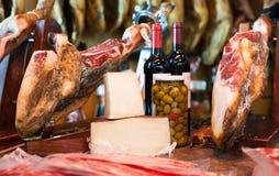 Wciąż życie hiszpański wieprzowiny jammon na właścicielu, butelkach wino ser i oliwkach, zdjęcia royalty free