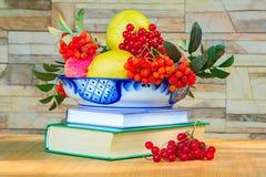 Wciąż życie: książki, owoc i jagody w pięknej wazie Obrazy Stock