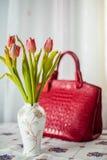 Wciąż życie skład w domowym wnętrzu na stole z tablecloth, tulipany w pięknej wazie na tle czerwony dam ` Fotografia Stock