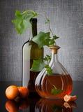 Wciąż życie skład z butelek mandarynkami na zmroku i liśćmi Fotografia Royalty Free