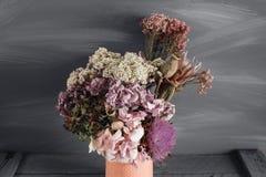 Wciąż życie wizerunek wysuszeni kwiaty w nieociosanej wazie przeciw wietrzejącemu drewnianemu tłu zdjęcie stock