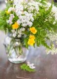 Wciąż życie z bukietów dzikimi kwiatami trawą na starej drewnianej zakładce i Fotografia Stock