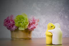 Wciąż życie z Ceramiczną lalą i kwiatem na drewnianym stole nad gru Fotografia Royalty Free