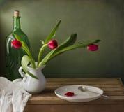 Wciąż życie z czerwonym tulipanem i bielu talerzem Zdjęcia Stock