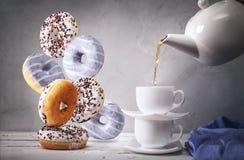 Wciąż życie z herbatą i spada puszków donuts Zdjęcie Royalty Free