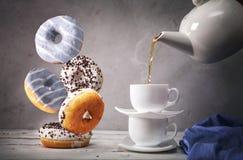 Wciąż życie z herbatą i spada puszków donuts Obraz Stock