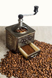 Wciąż życie z kawowymi fasolami i starym kawowym młynem na drewnianym tle Obrazy Stock