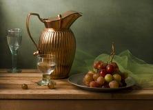 Wciąż życie z rocznika miotaczem i winogronami Zdjęcie Royalty Free