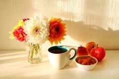 Wciąż życie z szklaną wazą z kolorowymi kwiatami peonie, filiżanka herbata, jabłczany dżem i jabłka na białym stole, zdjęcie stock
