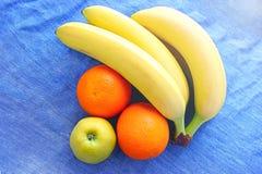 Wciąż życie z tropikalnymi owoc: banany, pomarańcze, na betonowej powierzchni w świetle słonecznym Obrazy Royalty Free
