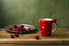 Wciąż życie z wiśniami i czerwoną filiżanką Obrazy Royalty Free
