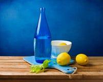 Wciąż życie z cytrynami i błękitny butelką Obrazy Royalty Free