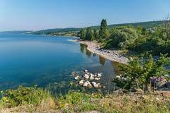 Wczasowiczki na kamiennym brzeg ogromny błękit rozjaśniają jezioro przeciw tłu zieleni pasma górskie Fotografia Stock