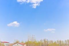 Wczesna wiosna z niebieskiego nieba i bielu chmurami Zdjęcia Stock