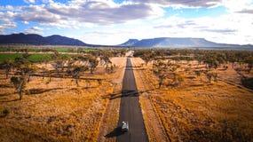 4wd旅行到艾瑞斯岩石的吉普旅途通过农村澳洲内地澳大利亚谷在有山的沙漠土地在backgrou 库存图片