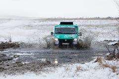 4WD集会卡车克服一个半冻池塘 免版税库存图片